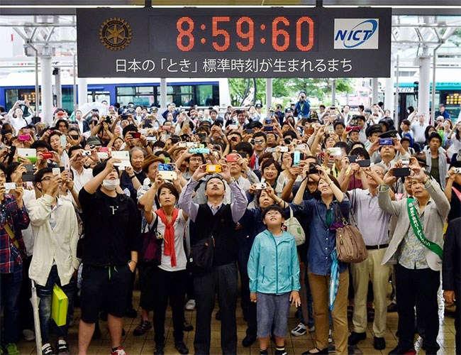 Geçtiğimiz yıl 1 Temmuz'da Tokyo'da artık saniyenin eklendiği anı fotoğraflamak için bekleyen kalabalık.