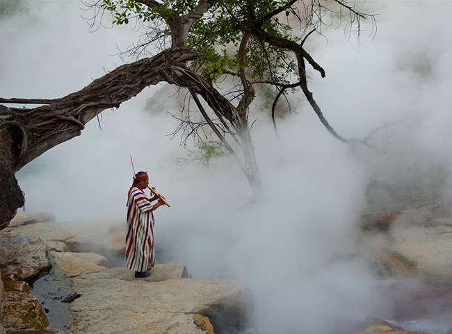"""Yerel inanışa göre Kaynayan Nehir muazzam spiritüel güce sahip bir mekân. Fotoğrafta bir şaman, """"taşların, ormanın ve tüm yaratılışın dualarını Yaradan'a ulaştırdığına"""" inandığı Duman Ruhu'na bir şarkı çalıyor."""